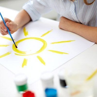 girl-with-brush-drawing-sun-on-paper-PND2R36.jpg
