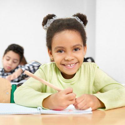 Schoolgirl smiling, posing in classroom at primary school